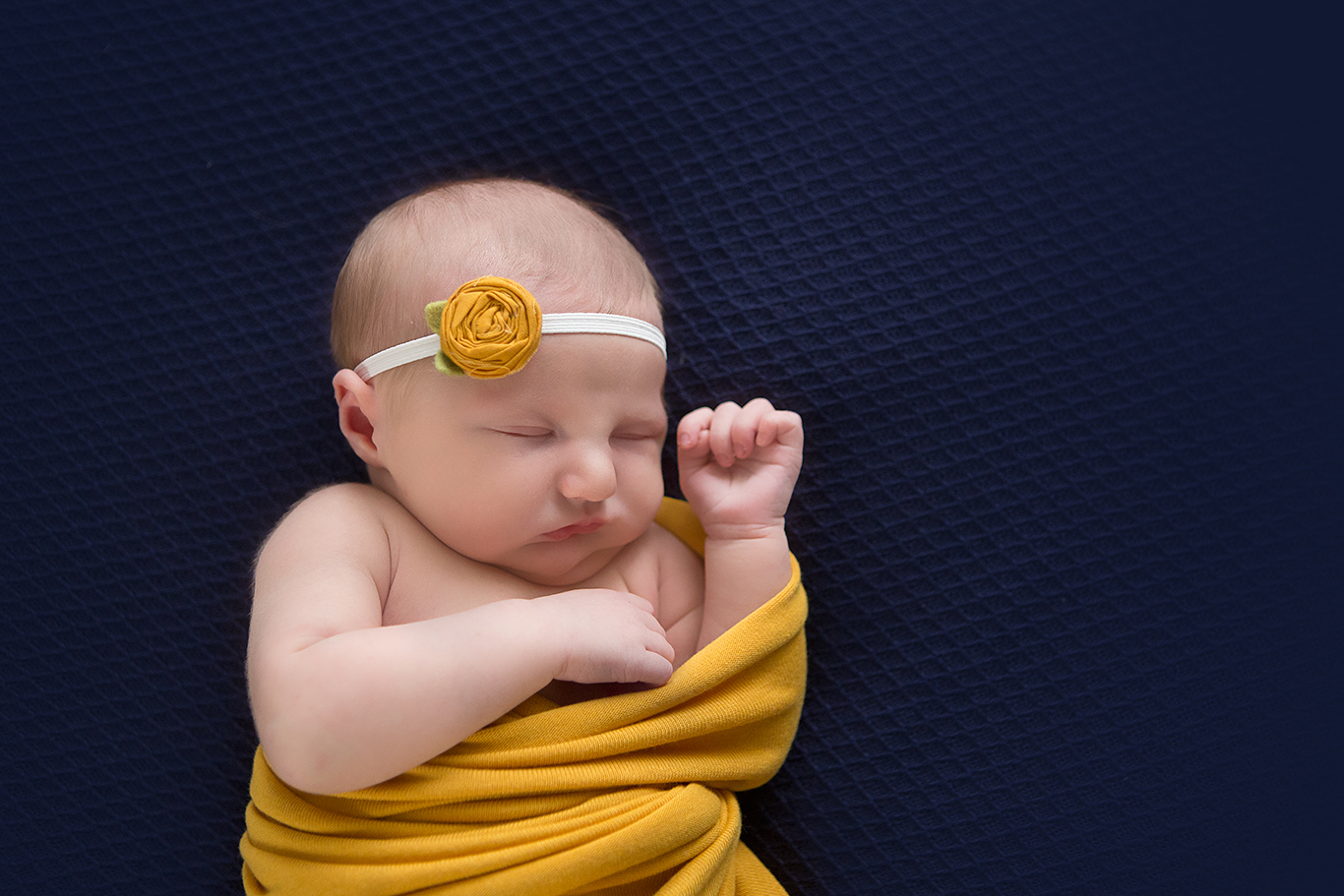 newborn sleeping in gold and blue